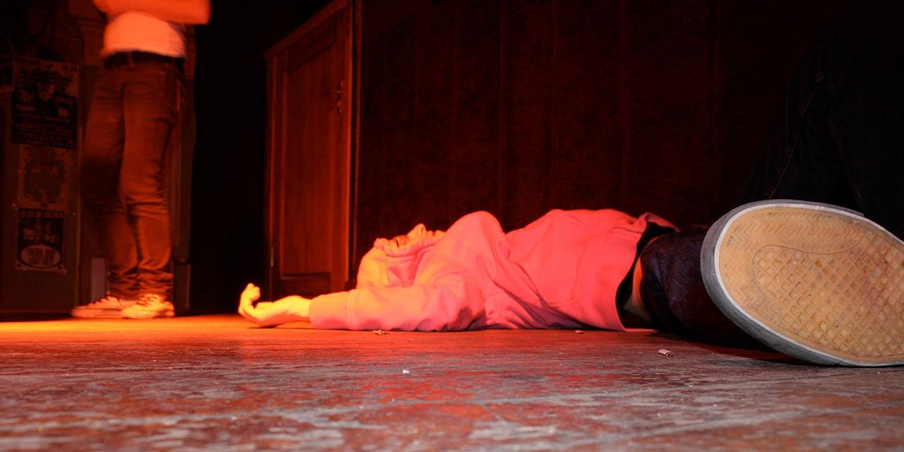 Typ liegt auf einer Bühne