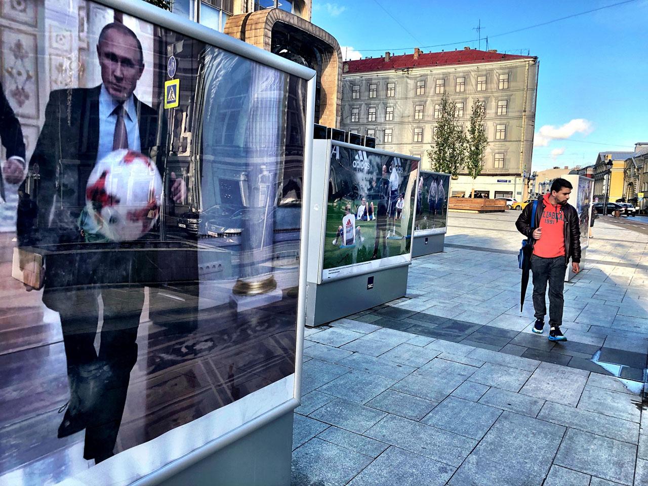 Mann geht an einem Putin-Poster vorbei