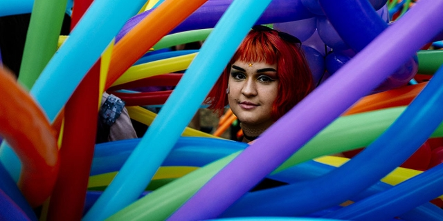 A participant looks through balloons during the 11th Gay Pride Parade in downtown Sofia