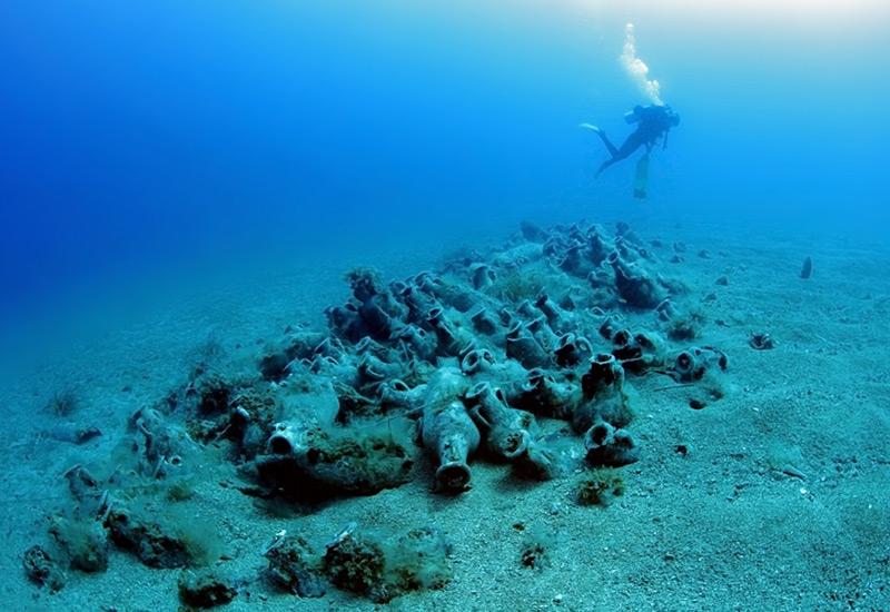 Taucher im Meer; auf dem Meeresboden: antike Amphoren