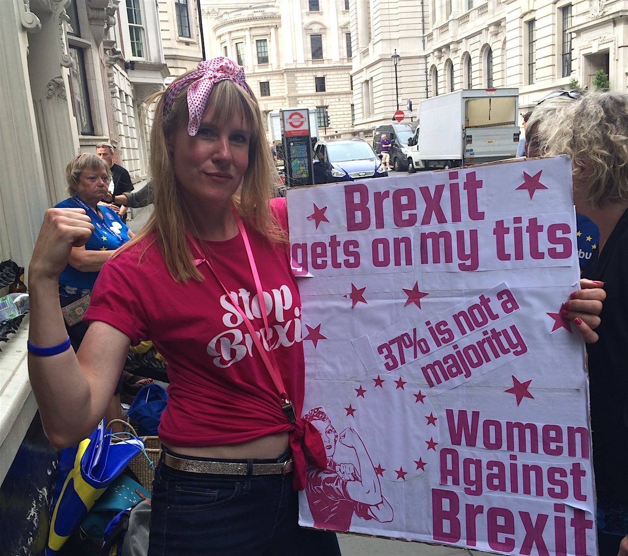 """Eine Frau trägt ein Plakat mit der Aufschrift """"Brexit gets on my tits"""", posiert davon wie die Frau auf dem legendären """"We Can Do It""""-Plakat."""