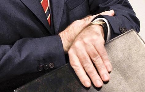 Ein Mann schaut auf seine Armbanduhr.