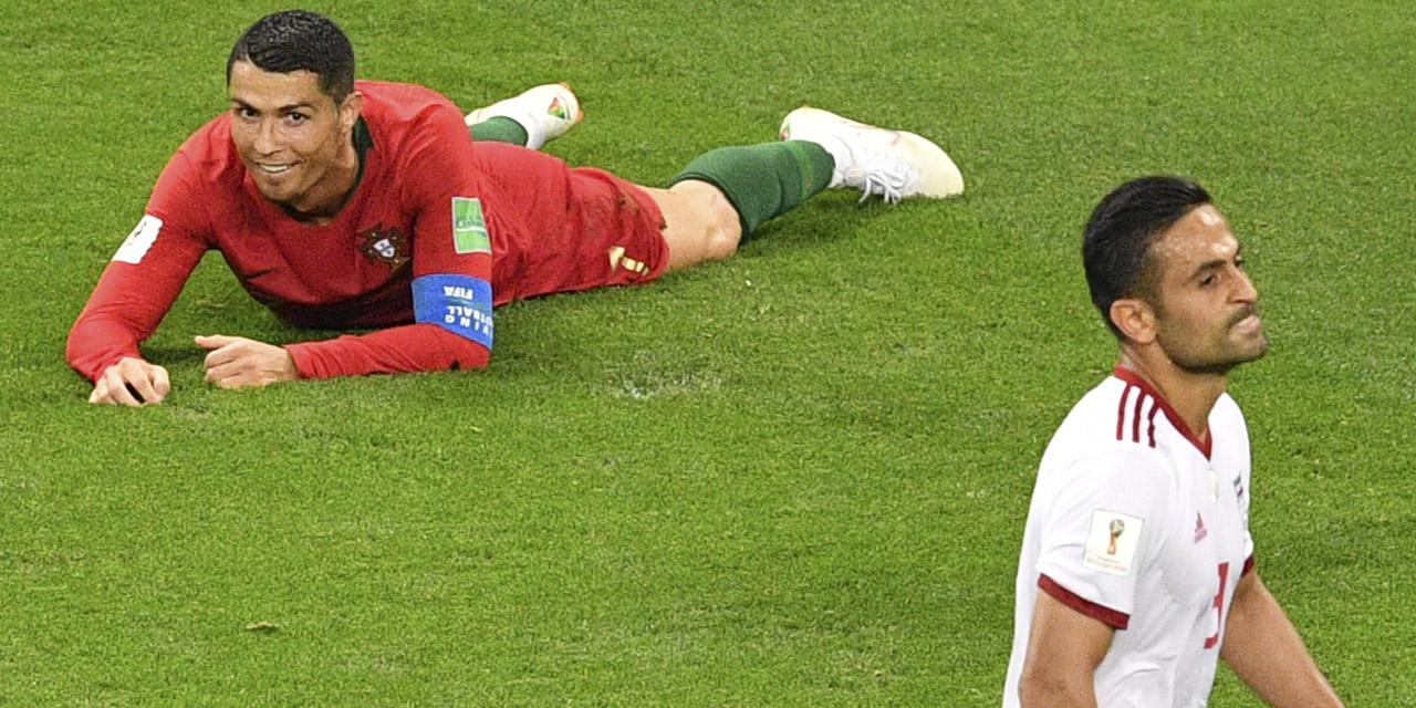 Ronaldo (Portugal) am Boden hinter Iran-Spieler