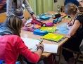 Schulkinder an Tischen mit Heften und Schultaschen