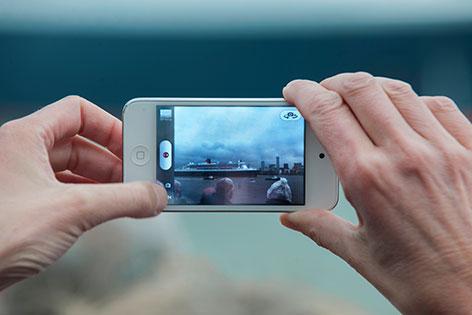 Mann macht Foto mit einem Smartphone