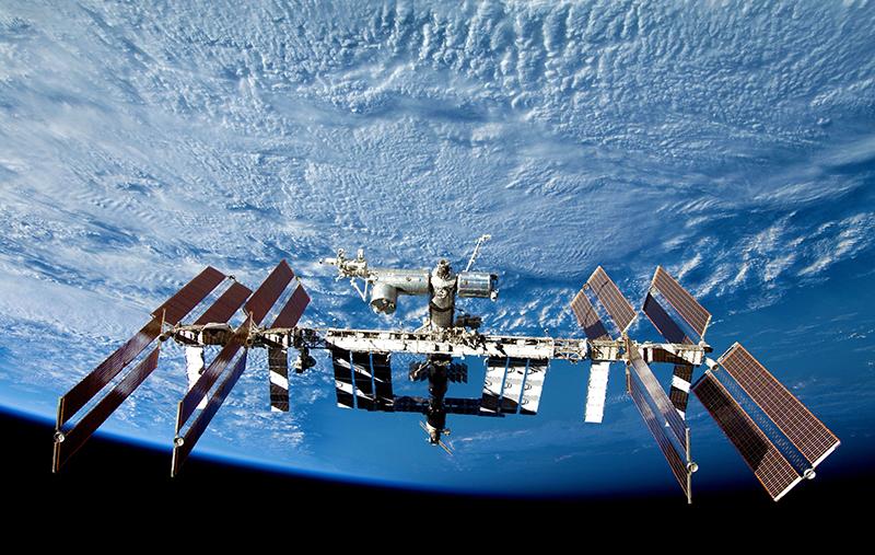 Schwerelos: Raumstation ISS über der wolkenbedeckten Erde