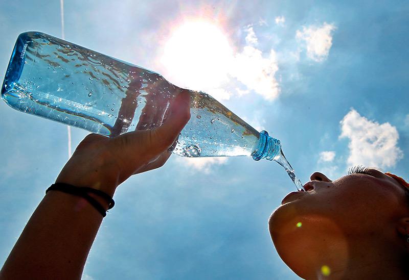 Sommerliche Hitze: Frau trinkt Wasser aus einer Glasflasche