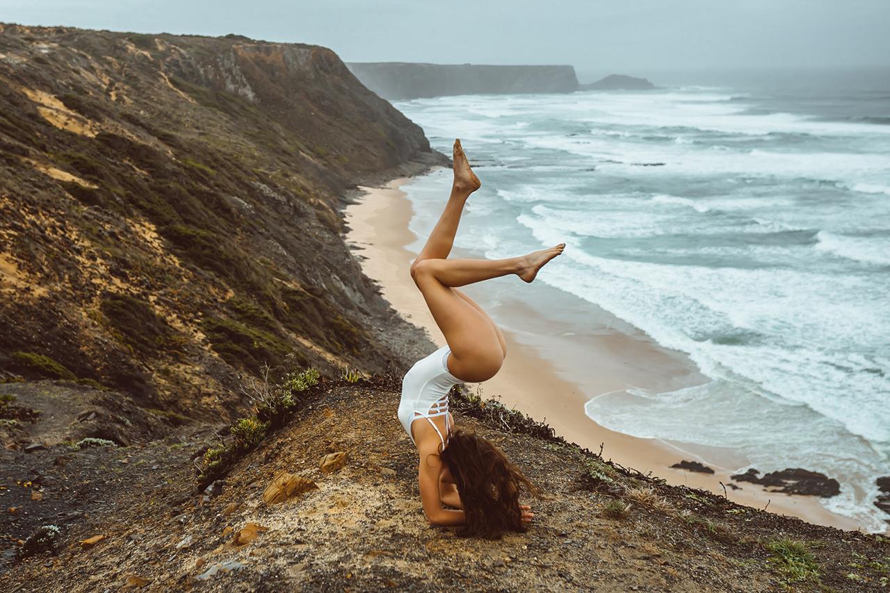 Sara Ticha macht Kopfstand vor einer Steilküste