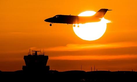 Ein Flugzeug landet bei Sonnenaufgang in Düsseldorf