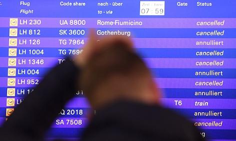 Ein Flugreisender vor einem Monitor, der annullierte Flüge anzeigt