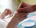Ein Mitarbeiter eines Alten-und Pflegeheims hält die Hand einer Bewohnerin.
