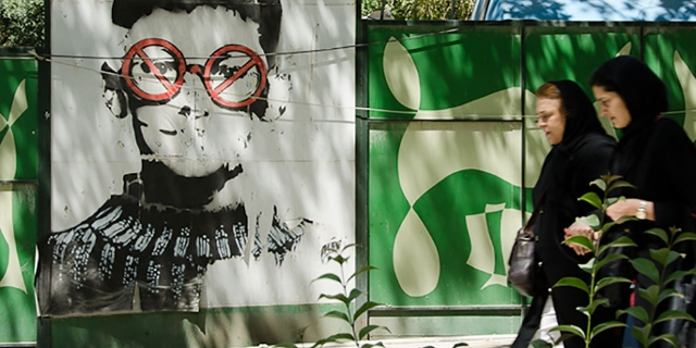 Straßenszene im Iran: Zwei Frauen gehen an einem Graffiti vorbei, das einen Buben zeigt mit Verbotszeichen vor den Augen