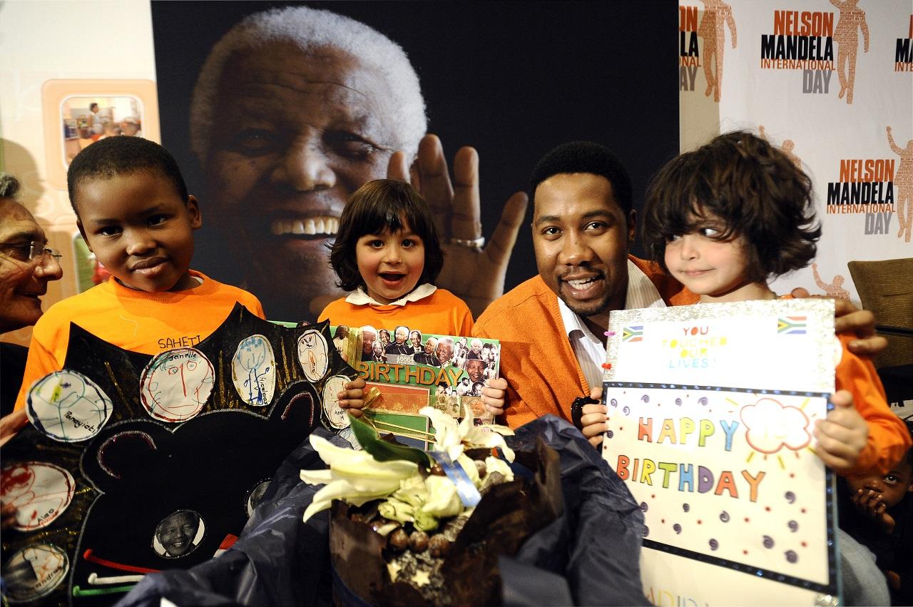 Ndaba Mandela mit Schulkindern 2011. Sie halten Happy Birthday-Schilder hoch zum 93. Geburtstag von Nelson Mandela
