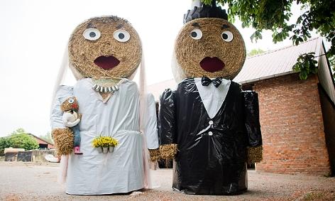 Ein Hochzeitspaar mit Baby als Strohfiguren