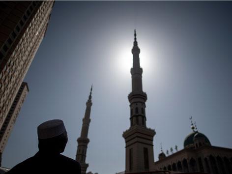 Das Minarett einer Moschee in China und ein betender Mann davor