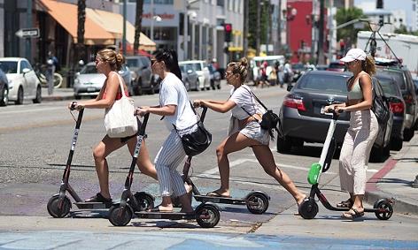 Junge Frauen fahren auf Elektroscootern über eine Kreuzung