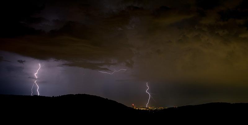 Nächtliche Blitze über der erleuchteten Großstadt