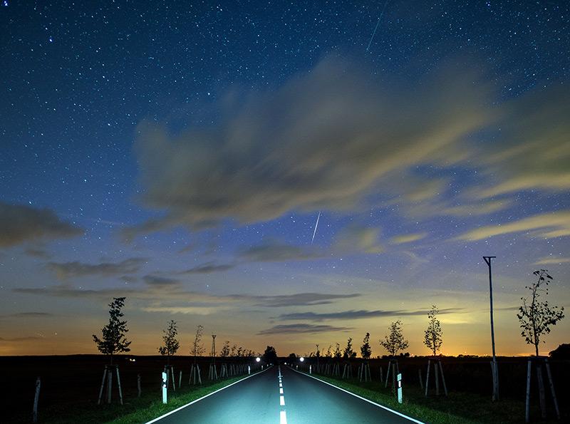 Nächtliche Landstraße; auf dem Himmel zeigt sich eine helle Sternschnuppe