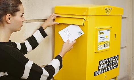 Frau wirft Brief in Postkasten