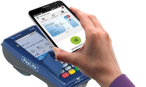 Eine Person hält ein Smartphone mit virtueller Bankomatkarte über ein Karten-Lesegerät.