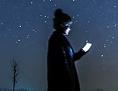 Frau mit Smartphone unter Sternenhimmel