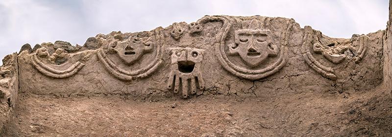 Historisches Steinrelief aus Peru mit Köpfen und Schlangen