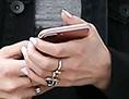 Frau mit Sonnenbrille geht auf der Straße und blickt auf ihr Handy