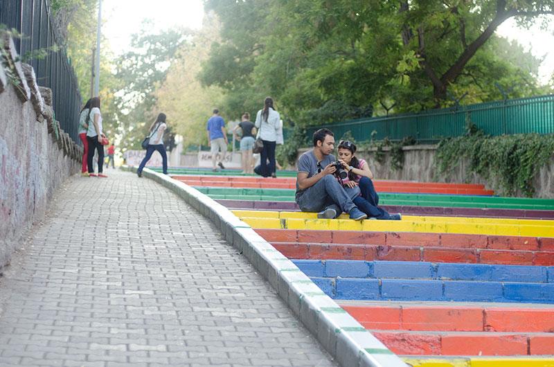 Menschen sitzen auf einer Treppe in Regenbogenfarben