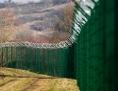 Ein grüner Grenzzaun zieht sich über Felder