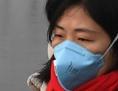 Chinesin und Chinese mit Atemschutzmaske an einem stark verschmutzten Tag in Peking, Jänner 2017