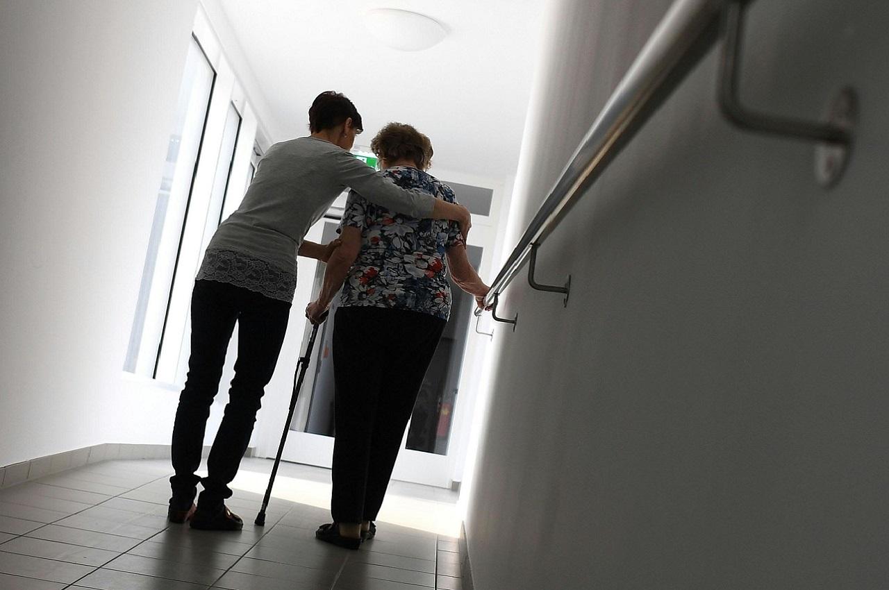 Eine Pflegerin hilft einer Frau mit Stock beim Gehen