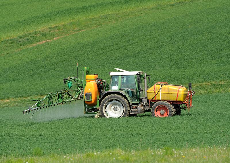 Ein Landwirt versprüht auf einem Feld ein Pflanzenschutzmittel.
