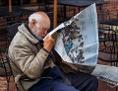 Ein amerikanischer alter Mann sitzt und liest Zeitung und sieht dabei aus, als würde er eingeschlafen sein