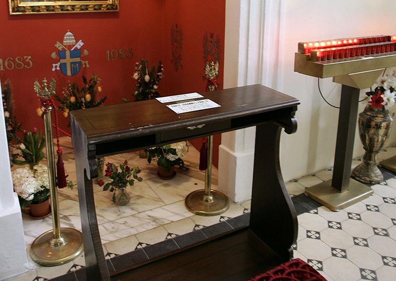 """Eine Kniebank mit der Aufschrift """"Papst Johannes Paul II. betete auf dieser Kniebank am 13. September 1983 aus Anlass des 300-Jahr-Jubiläums des Entsatzes von Wien"""" in der """"Sobieski-Kirche""""."""