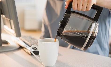 Ein Mann gießt aus einer Glaskanne Filterkaffee in eine Tasse