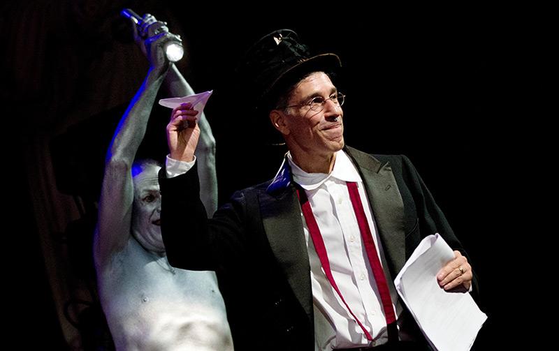 Zeremonienmeister Marc Abrahams wirft einen Papierflieger, im Hintergrund sein menschlicher Scheinwerfer