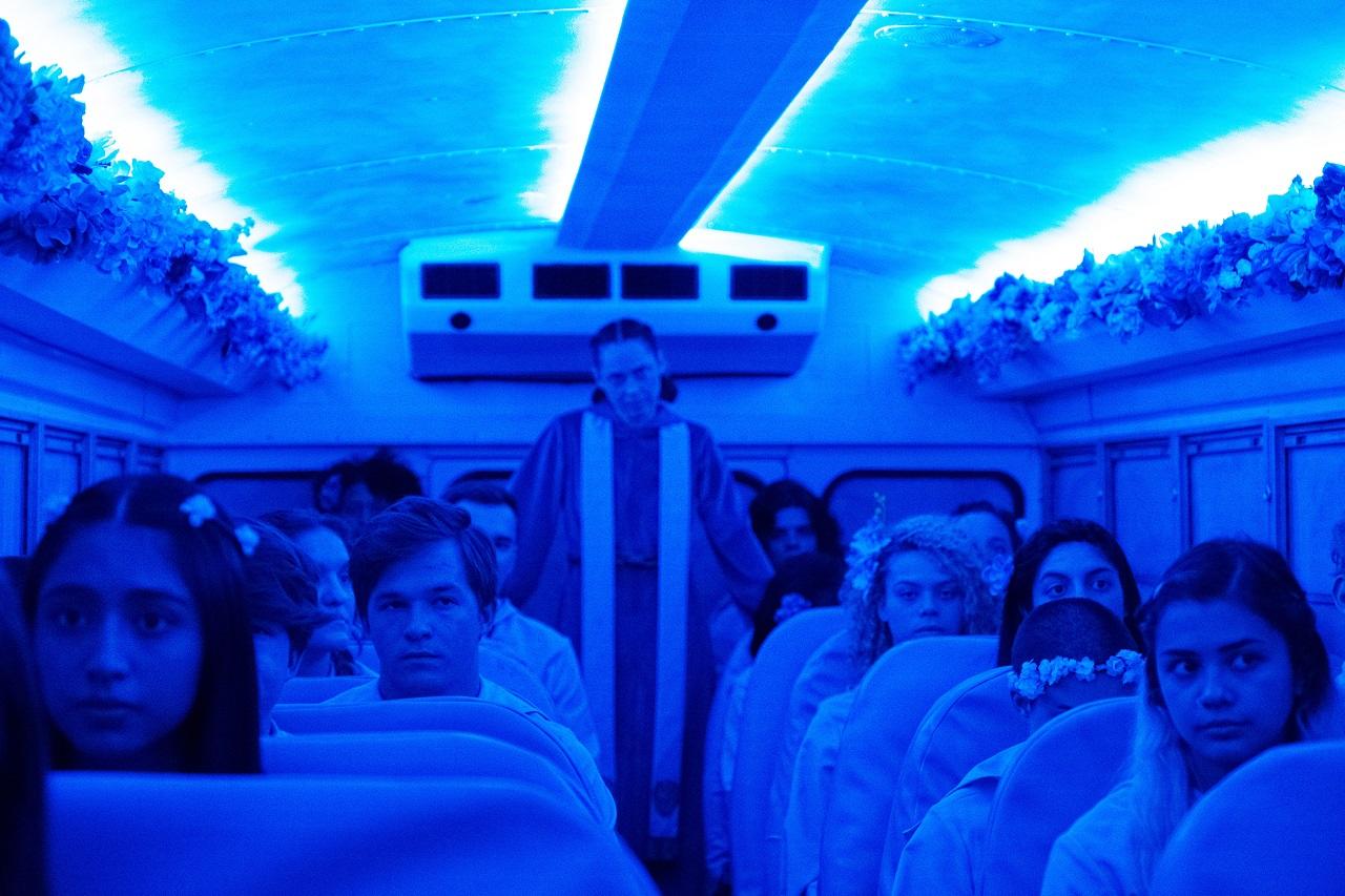 Mitglieder eines Kults in einen blauausgeleuchtetem Bus