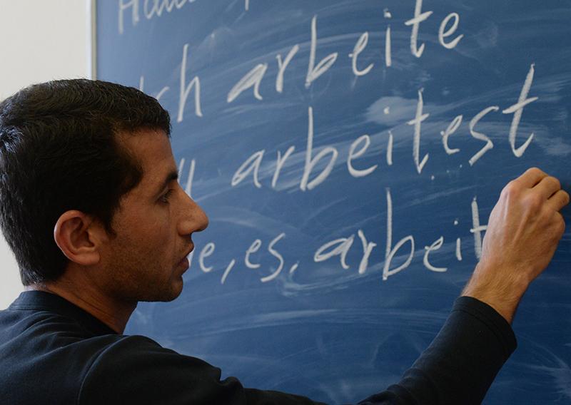 """Ein junger Mann aus Afghanistan konjugiert """"arbeiten"""" während einer Unterrichtseinheit eines Deutschkurses für Flüchtlinge."""
