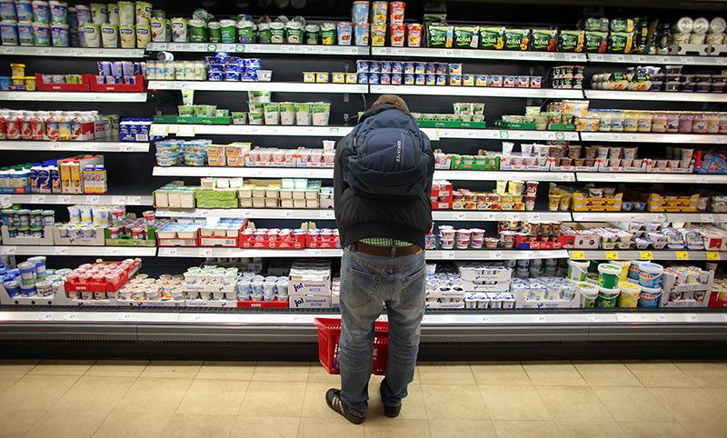 Junger Mann steht vor dem Kühlregal eines Supermarktes