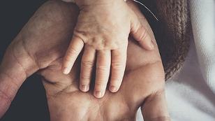 Kinderhand auf Erwachsenenhand