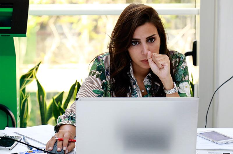 Eine Frau sitzt vor einem Computer und blickt ernst