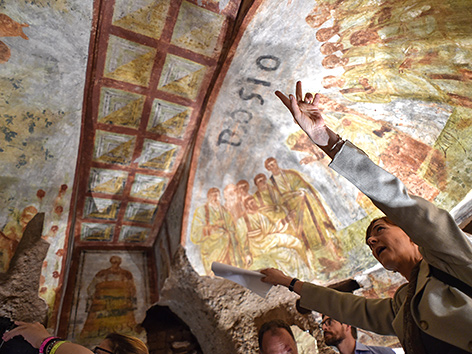 """Besucherinnen und Besucher in der 2017 renovierten Domitilla-Katakombe in Rom, zu sehen ist das Fresko """"Dei Fornai"""" (Die Bäcker)"""