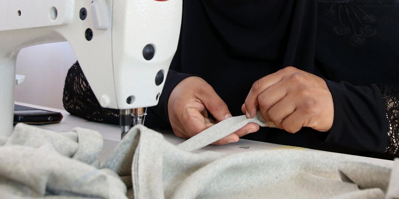 Eine Nähmaschine und Hände in Nahaufnahme