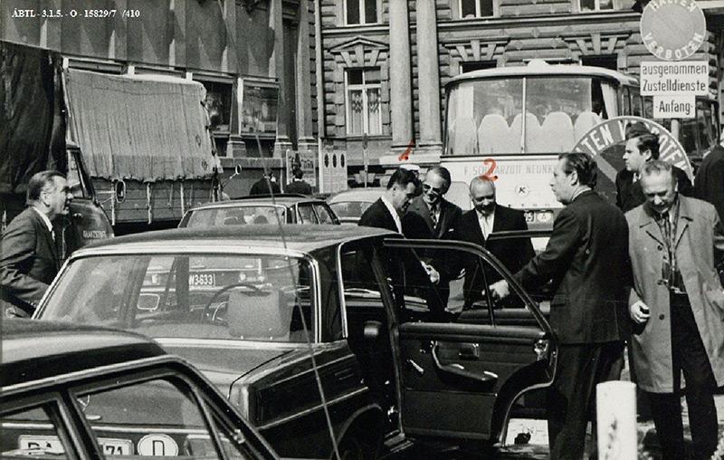 SW-Foto einer geheimdienstlichen Observierung: Männer in Anzügen neben einem geparkten Auto