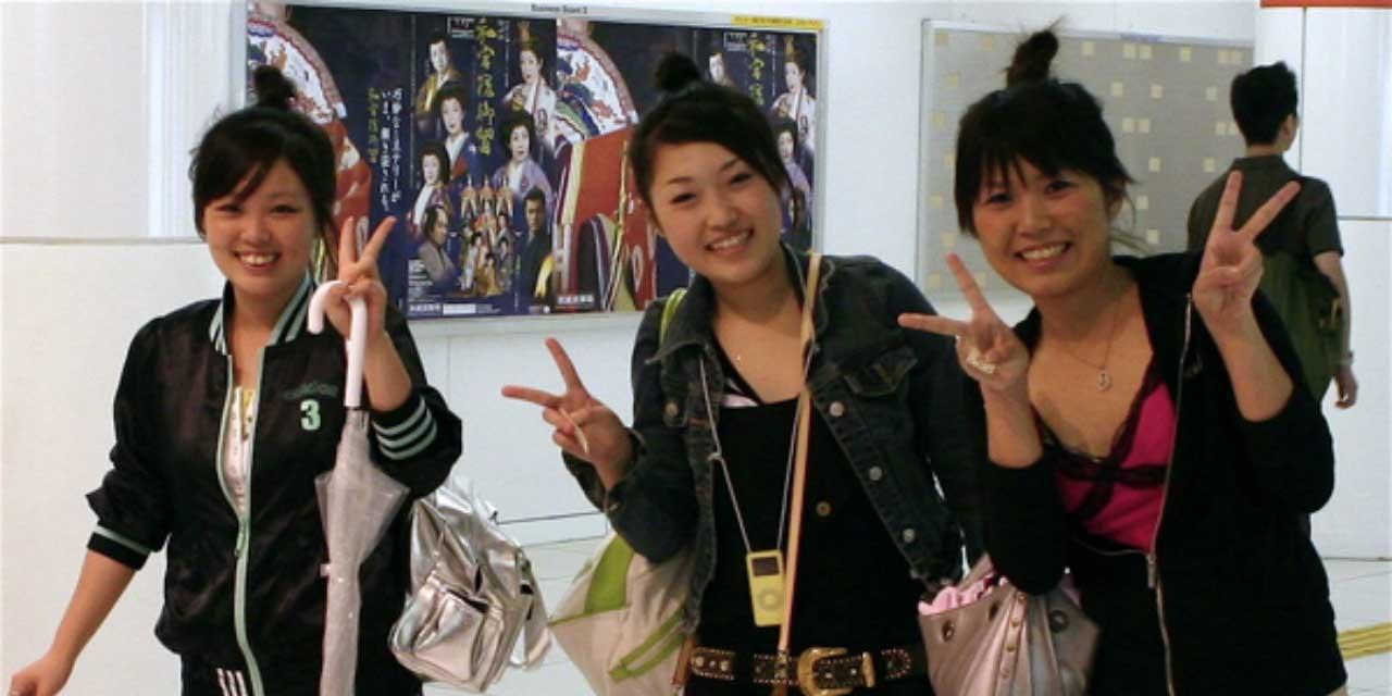 Frauen zeigen Victory-Symbol
