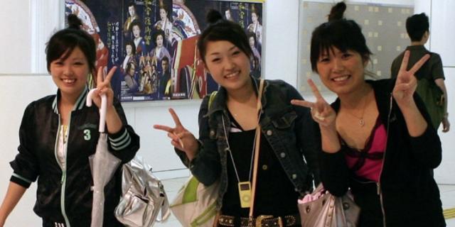 Japanische Frauen posieren mit Victory-Zeichen.