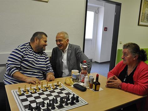 Caritas-Präsident Michael Landau mit zwei armutsbetroffenen Personen an einem Tisch mit einem Schachbrett
