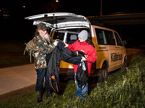 Eine Sozialarbeiterin überreicht einem obdachlosen Mann einen Schlafsack vor dem Caritas-Kältebus
