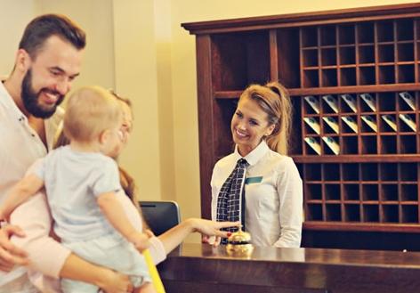 Familie checkt an Rezeption in Hotel ein