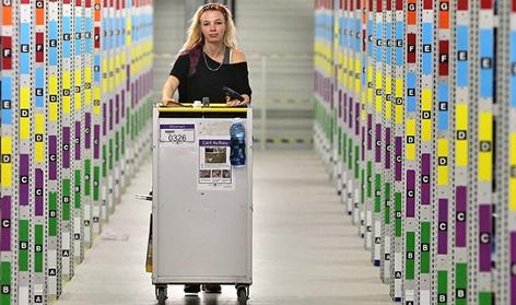 Mitarbeiterin in einem Amazon-Logistikzentrum fährt mit Wagerl durch riesige Halle mit Regalen voller Waren